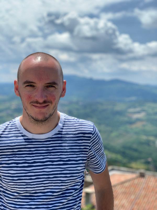 Philipp auf einem Berg mit grünem Tal im Hintergrund